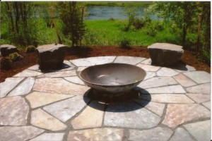 Flagstone patio with bowl fire pit and boulder seating